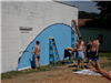 People paint a wall for community service