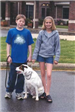 Two kids pose with a canine