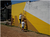 People paint a mural in Oil City for community service