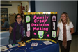 People stand by a Family Group Decision Making poster