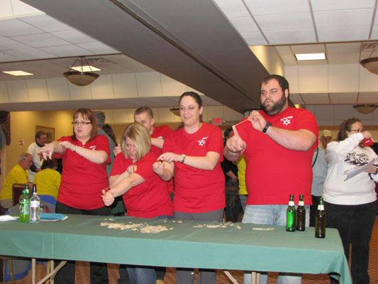 People stand at a table for a game at the Workforce Olympics 2014